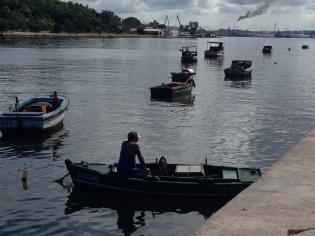 Fischer im Karibik-Outfit blickt auf Raffinerie